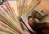 This picture taken on January 29 2016 in Lagos shows 1000 naira banknotes Nigeria's currency Nigeria's central bank governor Godwin Emefiele on...