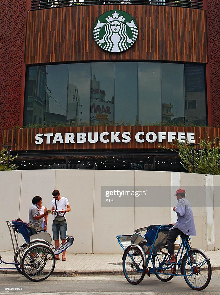 This picture taken on January 31, 2013 shows cyclo drivers waiting for customers outside the first Starbucks store in Vietnam, in Ho Chi Minh City, prior to its opening on February 1, 2013. Starbucks aims to have almost 4,000 stores in the Asia-Pacific by the end of 2013, including 1,000 in China.