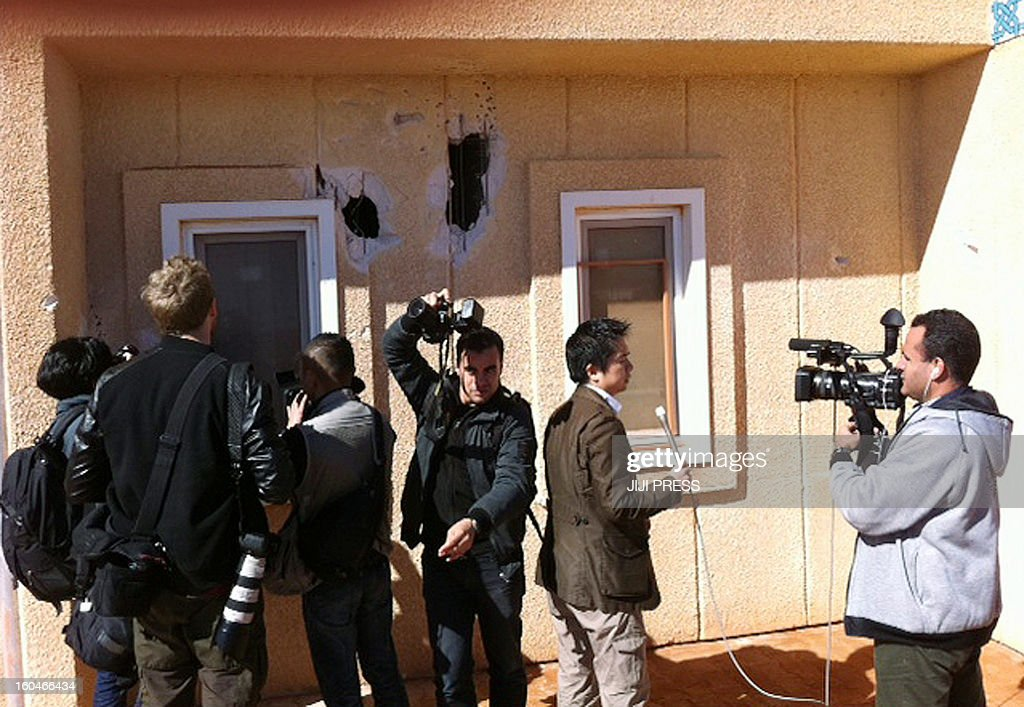 This picture taken on January 31, 2013 shows journalists reporting and taking photographs near a damaged wall at a desert gas plant after it opened for the press the first time after dozens of foreigners were killed during a four-day standoff that ended in a bloody showdown with Algerian commandos in In Amenas. Algeria has said 38 workers, out of which 37 were foreign, and 29 kidnappers died in the hostage taking.