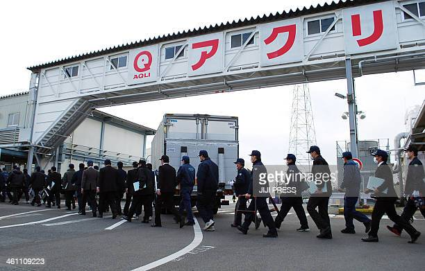This picture taken on January 4 2014 shows police investigators entering the Gunma factory of Japanese frozen foods company Aqli Foods a subsidiary...