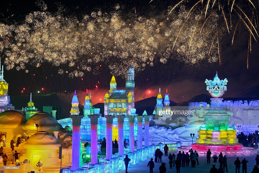 This picture taken on January 5, 2013 shows people visiting Ice and Snow World as fireworks fill the sky at the opening ceremony of the 2013 Harbin Internatoinal Ice and Snow Festival in Harbin, in northeast China's Heilongjiang province. This year's 'Ice and Snow World' features majestic ice castles and sculptures of fairytale characters equipped with LED lights, bringing a colourful and warm aura to the icy wonderland. CHINA OUT AFP PHOTO