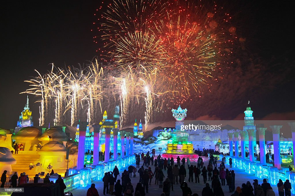 This picture taken on January 5, 2013 shows people visiting Ice and Snow World as fireworks fill the sky at the opening ceremony of the 2013 Harbin Internatoinal Ice and Snow Festival in Harbin, in northeast China's Heilongjiang province. This year's 'Ice and Snow World' features majestic ice castles and sculptures of fairytale characters equipped with LED lights, bringing a colourful and warm aura to the icy wonderland. CHINA