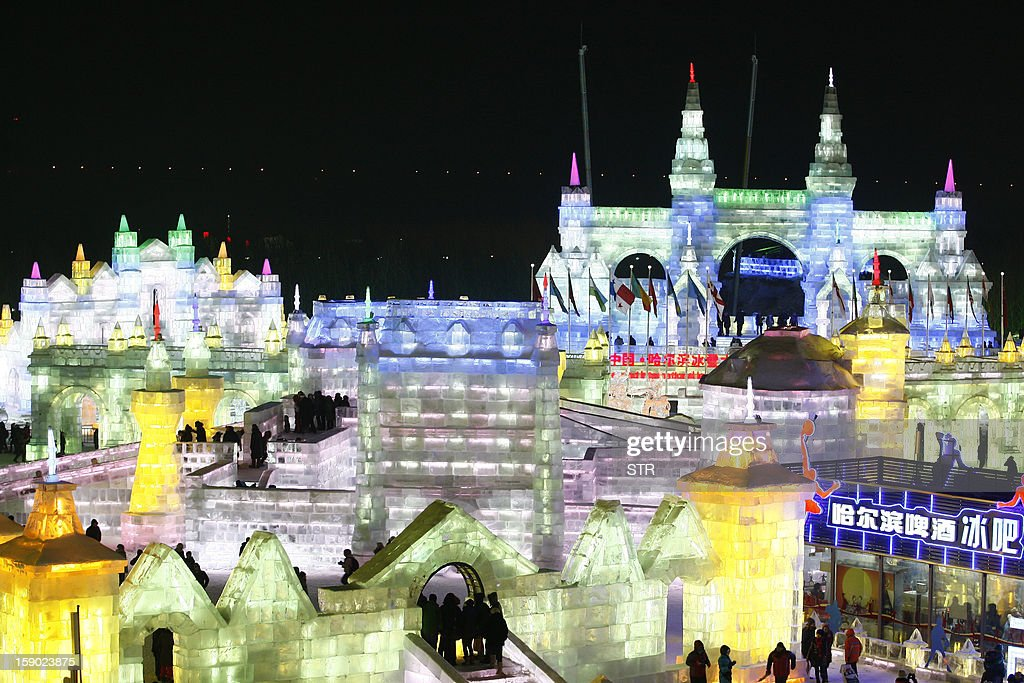 This picture taken on January 5, 2013 shows people visiting Ice and Snow World during the opening ceremony of the 2013 Harbin International Ice and Snow Festival in Harbin, in northeast China's Heilongjiang province. This year's 'Ice and Snow World' features majestic ice castles and sculptures of fairytale characters equipped with LED lights, bringing a colourful and warm aura to the icy wonderland. CHINA