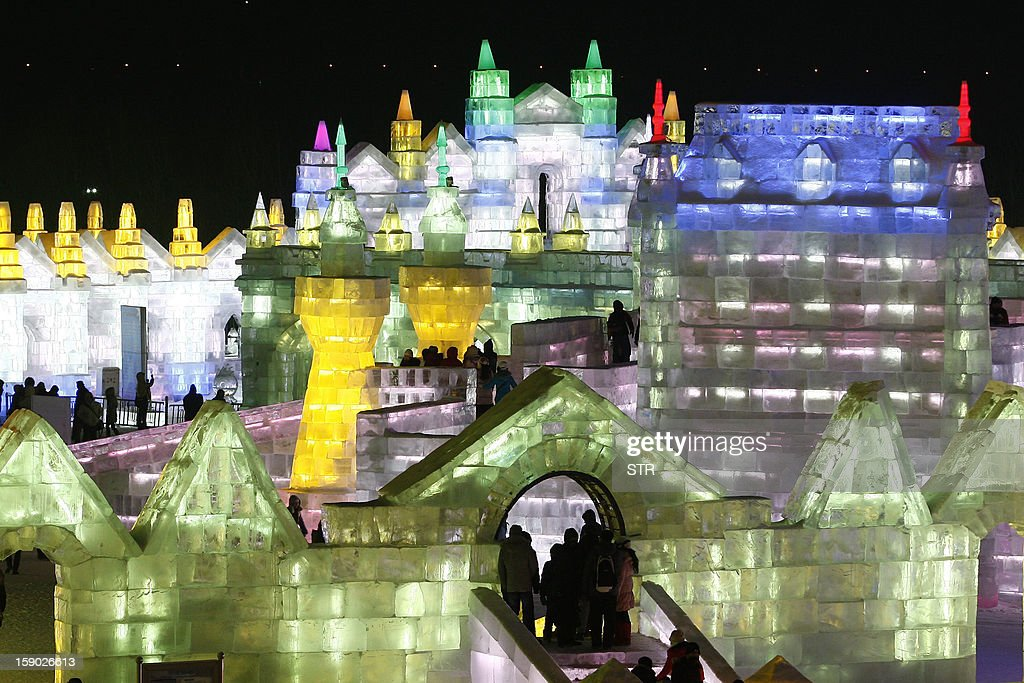 This picture taken on January 5, 2013 shows people visiting Ice and Snow World during the opening ceremony of the 2013 Harbin International Ice and Snow Festival in Harbin, in northeast China's Heilongjiang province. This year's 'Ice and Snow World' features majestic ice castles and sculptures of fairytale characters equipped with LED lights, bringing a colourful and warm aura to the icy wonderland. CHINA OUT AFP PHOTO
