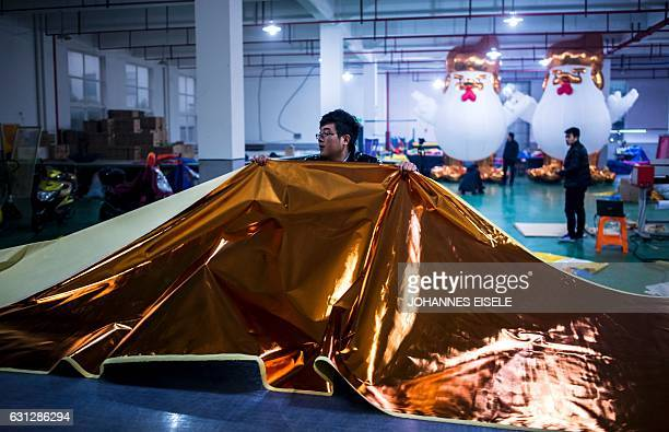 This picture taken on January 6 2017 shows a worker cutting fabric for inflatable chickens resembling Donald Trump in a factory in Jiaxing A Chinese...