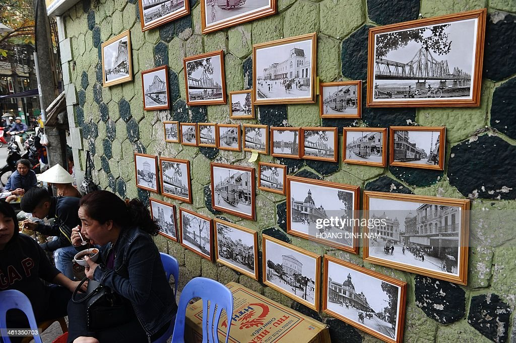 This picture taken on January 7, 2014 shows copies of old black and white photographs of Hanoi city in the early 20th century during French colonial rule hung on a wall for sale in the ancient quarter of Hanoi. AFP PHOTO/HOANG DINH Nam