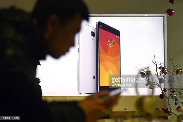 This picture taken on January 7 2015 shows a man using a mobile phone at a Xiaomi shop in Beijing AFP PHOTO / WANG ZHAO / AFP / WANG ZHAO