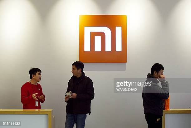 This picture taken on January 7 2015 shows a staff member of Xiaomi speaking to a customer at a Xiaomi shop in Beijing AFP PHOTO / WANG ZHAO / AFP /...