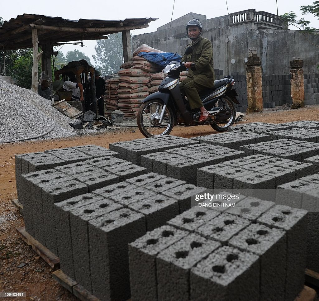 This picture taken on January 8, 2013 shows a motorcyclist riding past a workshop that produces bricks made of stone and cement at a village in Trieu Son district, north-central province of Thanh Hoa. In order to save agricultural land and to protect the environment from toxic smoke produced by tileries, people are advised to reduce using traditional terracotta bricks in building houses. AFP PHOTO / HOANG DINH Nam
