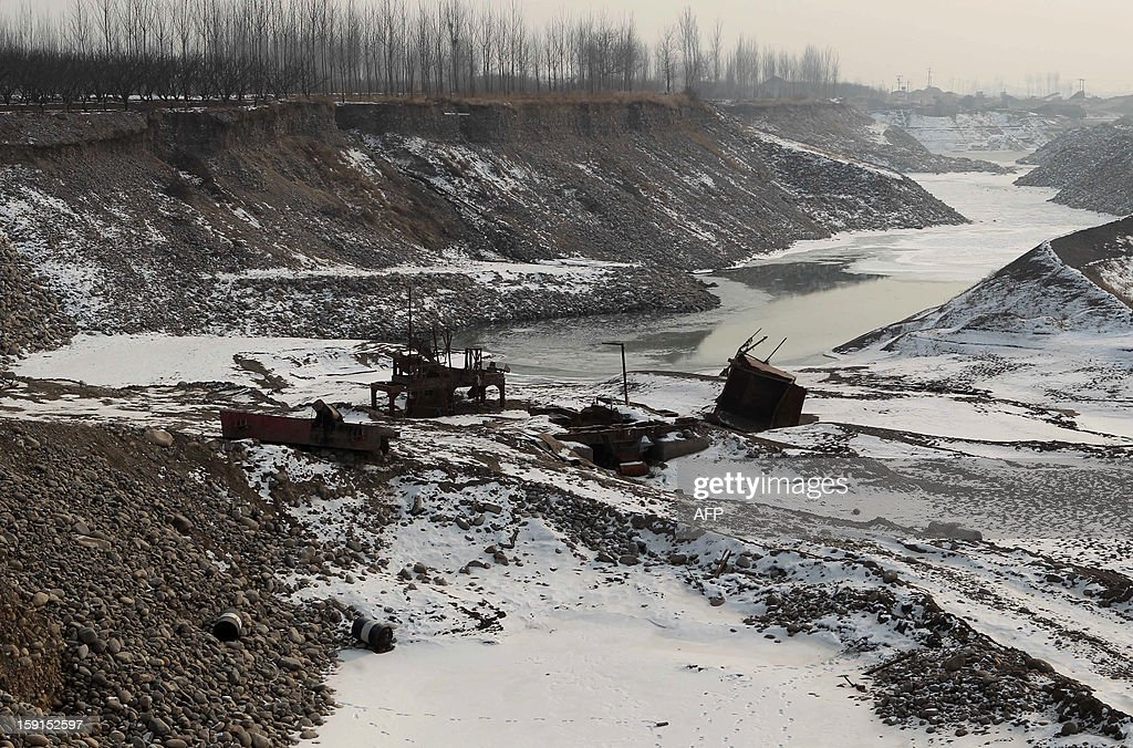 This picture taken on January 8, 2013 shows discarded machinery parts left in the Juma river after gravel mining operations in Beijing, which greatly influences the flood discharge of the river. Many waterways in China have become heavily contaminated with toxic waste from factories and farms -- pollution blamed on more than three decades of rapid economic growth and lax enforcement of environmental protection laws. CHINA OUT AFP PHOTO