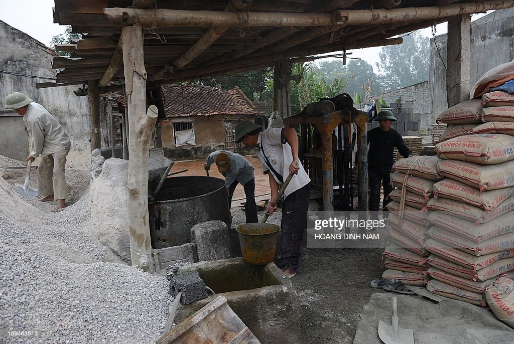This picture taken on January 8, 2013 shows labourers at a workshop that produces bricks made of stone and cement at a village in Trieu Son district, north-central province of Thanh Hoa. In order to save agricultural land and to protect the environment from toxic smoke produced by tileries, people are advised to reduce using traditional terracotta bricks in building houses. AFP PHOTO / HOANG DINH Nam