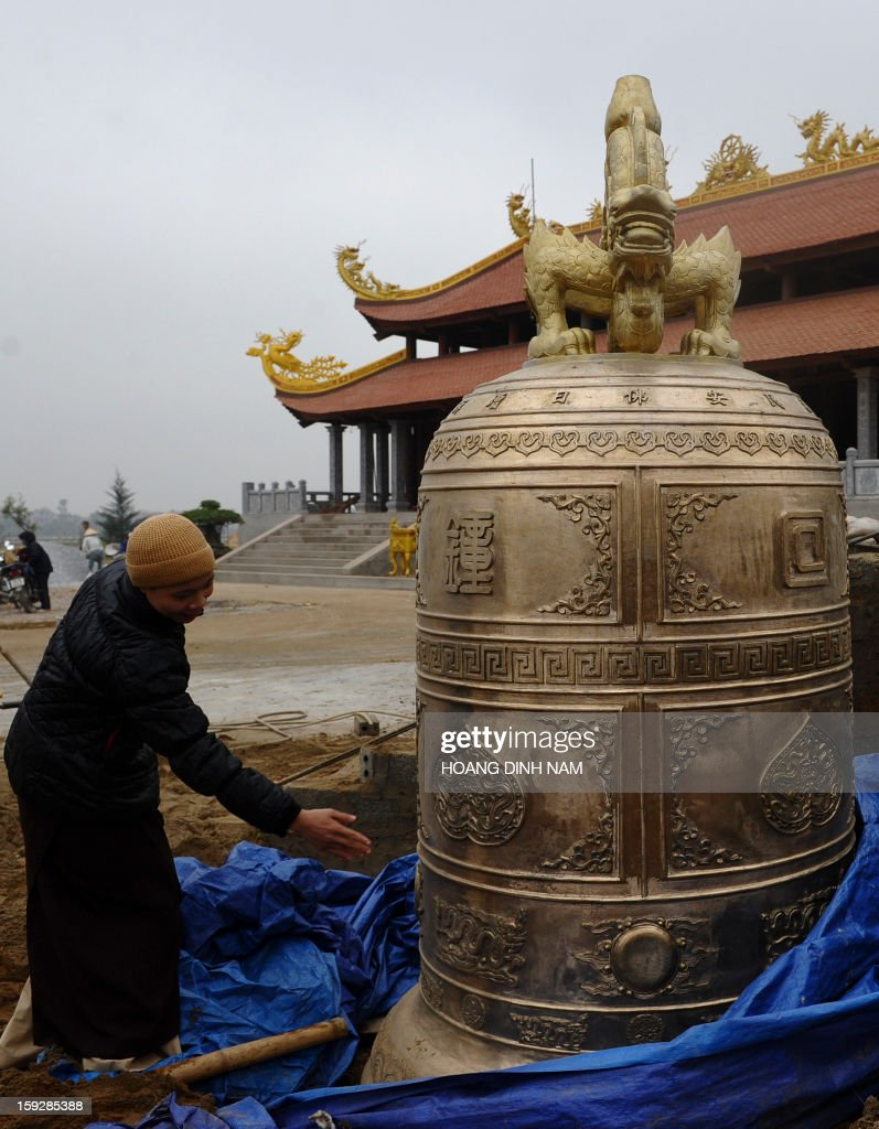 This picture taken on January 8, 2013 shows nun Thich Dam Ngoan inspecting a newly molded bell on the site of the new pagoda of Hoi Long under construction at Hoang Hoa district, in the northern province of Thanh Hoa. Many new buddhist pagodas have been built in recent years throughout the country with agreement from communist authorities. AFP PHOTO/HOANG DINH Nam