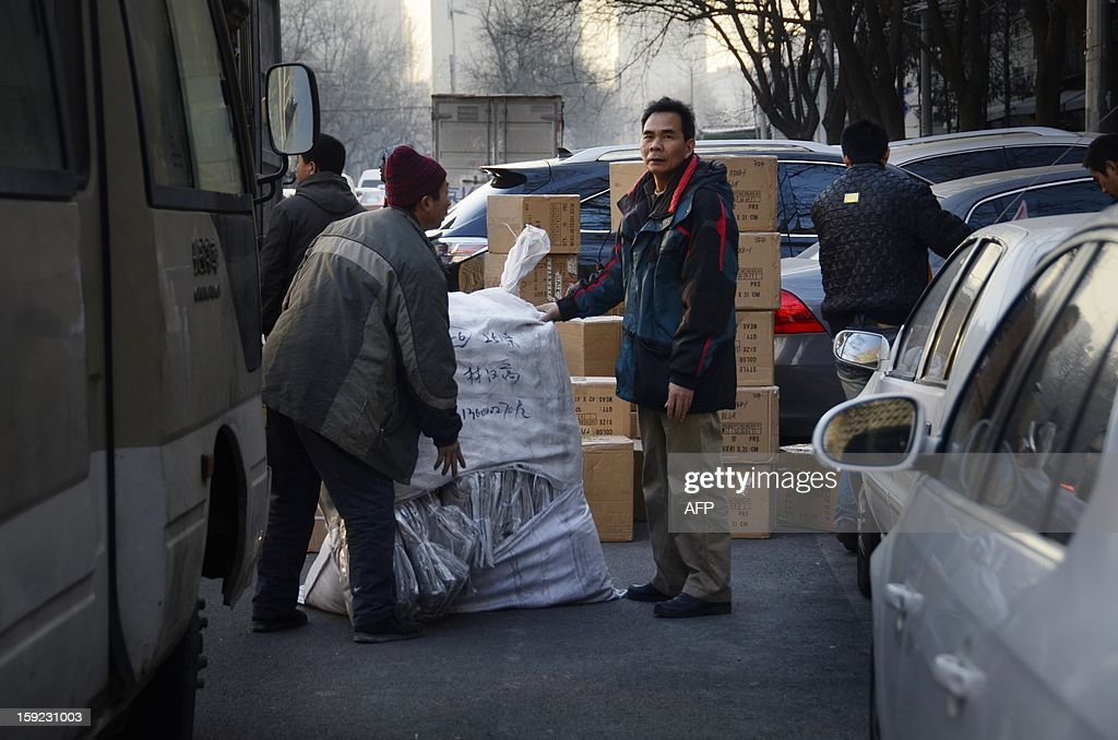 This picture taken on January 9, 2013 shows a Chinese man looking on as he checks boxes next to a delivery truck outside a market in Beijing. China's trade surplus surged in 2012, but total imports and exports grew slowly owing to weakness at home and abroad, official data showed on January 10, while analysts warned of another tough year ahead.