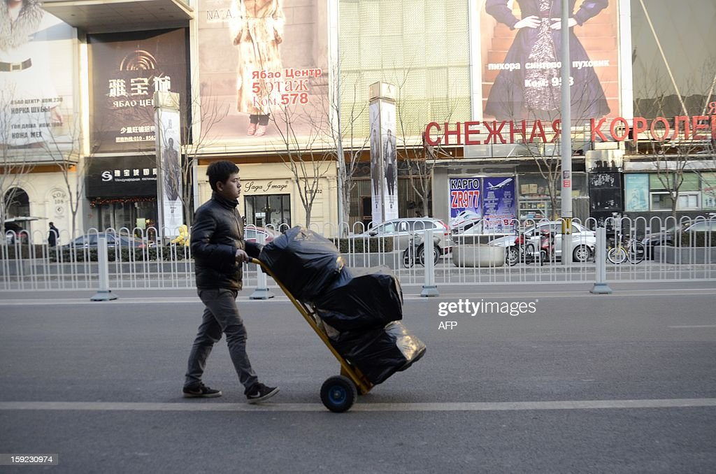 This picture taken on January 9, 2013 shows a Chinese man pushing a cart as he walks along a street outside a market in Beijing. China's trade surplus surged in 2012, but total imports and exports grew slowly owing to weakness at home and abroad, official data showed on January 10, while analysts warned of another tough year ahead.
