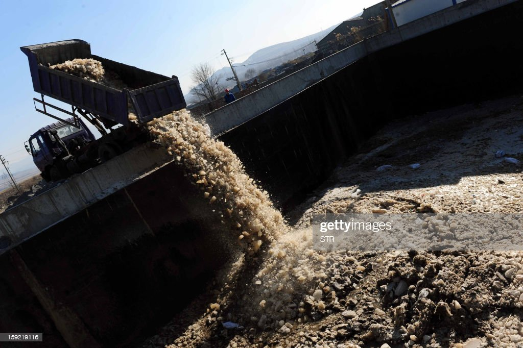 This picture taken on January 9, 2013 shows a truck dumping waste water and waste ice into an emergency waste water pool after companies from Tianji Coal Chemical Industry Group leaked nearly nine tons of aniline into a river in Lucheng, in central China's Shanxi province on December 31, 2012. The leak affected downstream cities in neighboring Hebei and Henan provinces, causing water supply crisis to households in the following days. CHINA