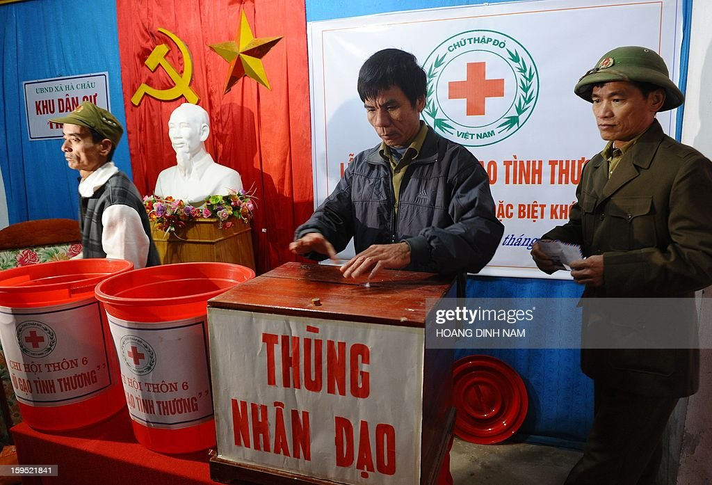 This picture taken on January 9, 2013 shows villagers including former soldiers contributing money to the project of building up a 'shared rice pot' for poor families launched by the local Red Cross society at a village in Ha Trung district, North-central province of Thanh Hoa. Vietnam's poverty rate is likely to reach 20,7 percent this year if caculated to new standards as recommended by the World Bank. Under the new standards, the poverty line is 2.24 US per person per day. AFP PHOTO/HOANG DINH Nam