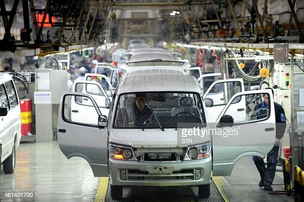 This picture taken on January 9 2015 shows workers assembling automobiles on the assembly line in a factory workshop in Shenyang northeast China's...