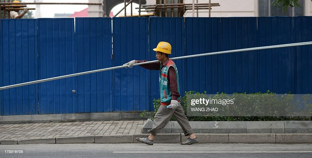 This picture taken on July 11, 2013 shows a Chinese worker carrying steel tubes near a construction site in Beijing. China's economic growth dropped to 7.5 percent in the second quarter of this year, analysts predicted in an AFP survey ahead of fresh GDP figures Monday, projecting a further slowdown for the world's second-largest economy.