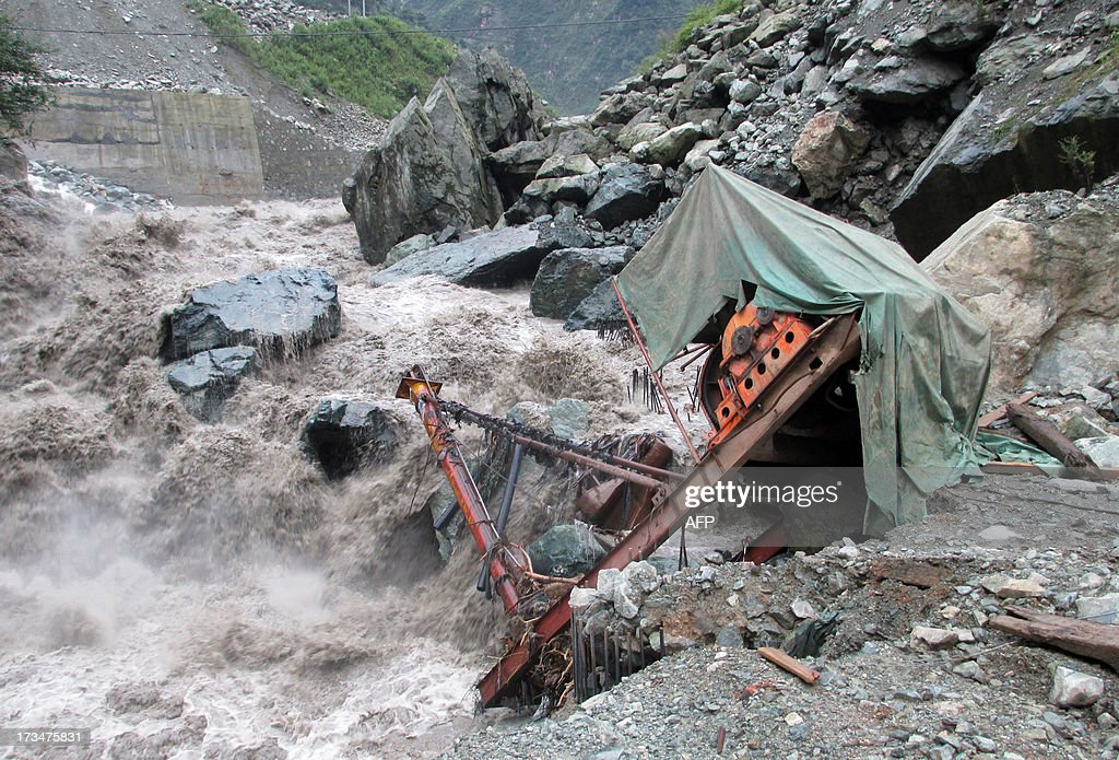 This picture taken on July 11 2013 shows a machine being washed away by floodwaters in Wolong National Nature Reserve southwest China's Sichuan...