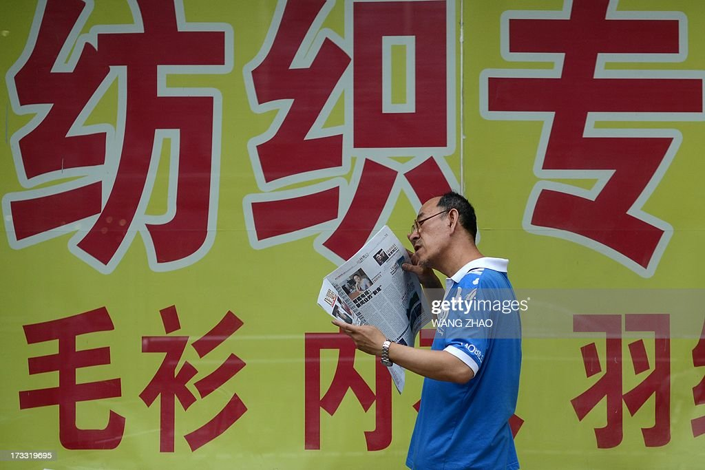 This picture taken on July 11, 2013 shows a man reading a newspaper outside a shop in Beijing. China's economic growth dropped to 7.5 percent in the second quarter of this year, analysts predicted in an AFP survey ahead of fresh GDP figures Monday, projecting a further slowdown for the world's second-largest economy. AFP PHOTO / WANG ZHAO