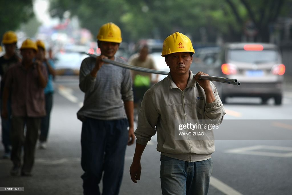 This picture taken on July 11, 2013 shows Chinese workers carrying steel tubes near a construction site in Beijing. China's economic growth dropped to 7.5 percent in the second quarter of this year, analysts predicted in an AFP survey ahead of fresh GDP figures Monday, projecting a further slowdown for the world's second-largest economy.