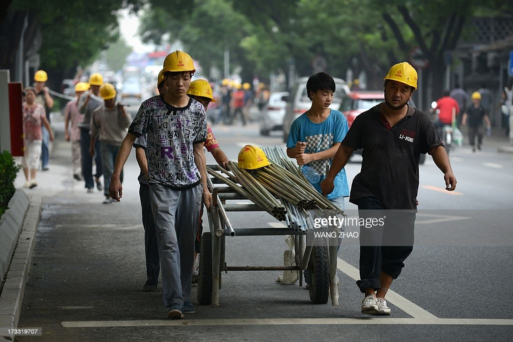 This picture taken on July 11, 2013 shows Chinese workers pulling steel tubes near a construction site in Beijing. China's economic growth dropped to 7.5 percent in the second quarter of this year, analysts predicted in an AFP survey ahead of fresh GDP figures Monday, projecting a further slowdown for the world's second-largest economy. AFP PHOTO / WANG ZHAO