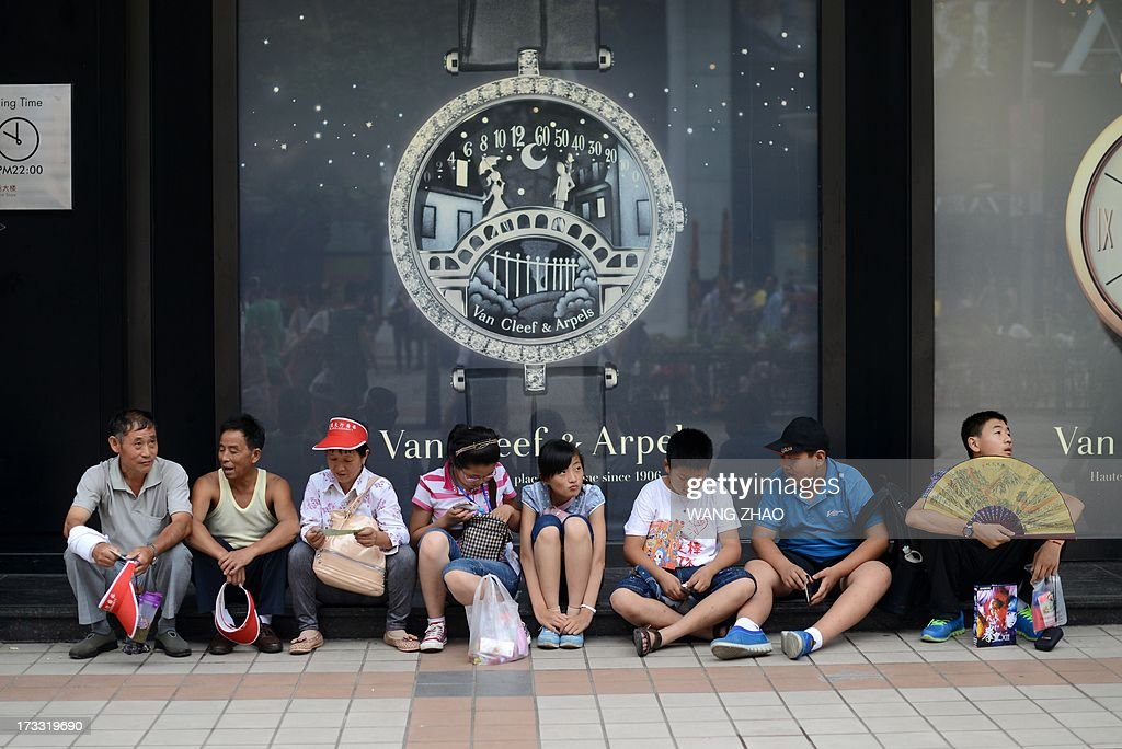 This picture taken on July 11, 2013 shows people resting outside a shop in Beijing. China's economic growth dropped to 7.5 percent in the second quarter of this year, analysts predicted in an AFP survey ahead of fresh GDP figures Monday, projecting a further slowdown for the world's second-largest economy. AFP PHOTO / WANG ZHAO