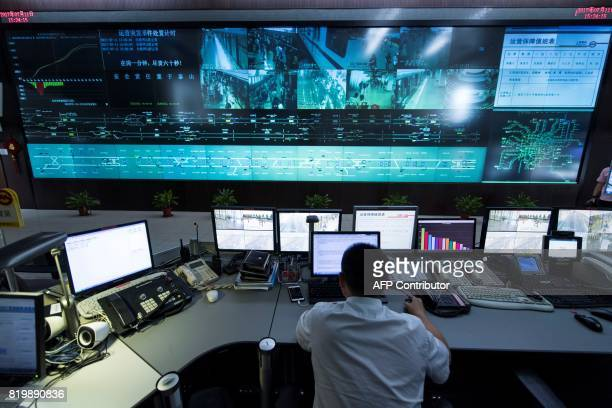 This picture taken on July 11 2017 shows a man working at the central command centre of the Shanghai metro system Deep underneath Shanghai workers on...