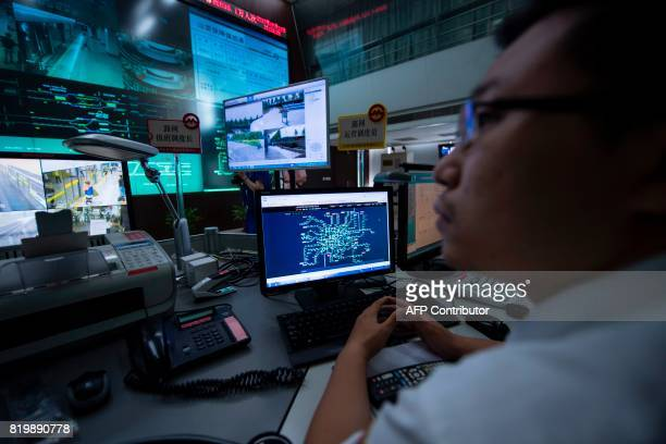 This picture taken on July 11 2017 shows a man working in the central command centre of the Shanghai metro system Deep underneath Shanghai workers on...