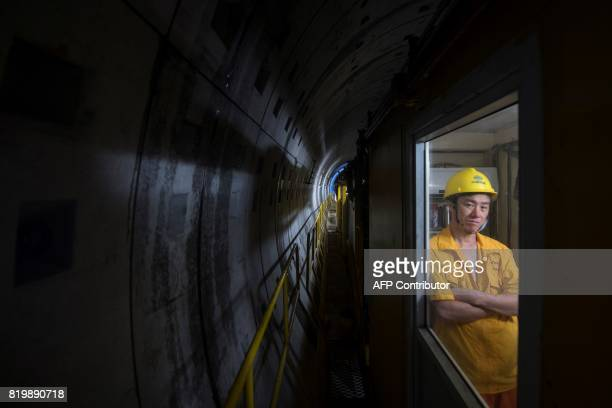 TOPSHOT This picture taken on July 11 2017 shows a worker looking out of a train at the construction site of Line 14 of the Shanghai metro system...