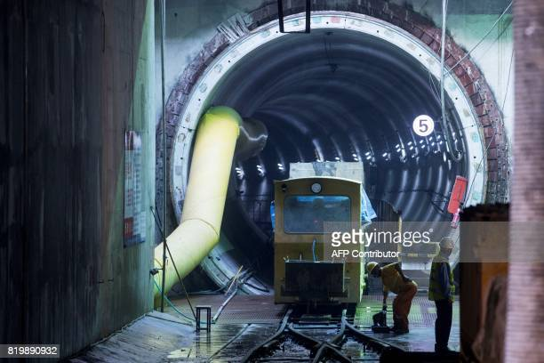 This picture taken on July 11 2017 shows a worker looking out of a train at the construction site of Line 14 of the Shanghai metro system Deep...