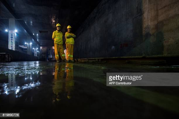 This picture taken on July 11 2017 shows two workers standing at the construction site of Line 14 of the Shanghai metro system Deep underneath...