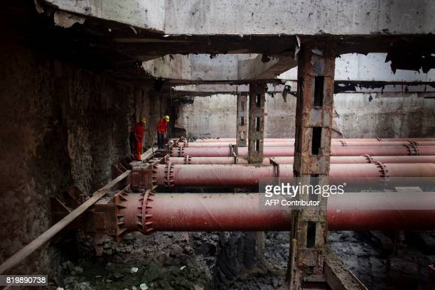 This picture taken on July 11 2017 shows two workers standing on pipes at the construction site of Line 14 of the Shanghai metro system Deep...
