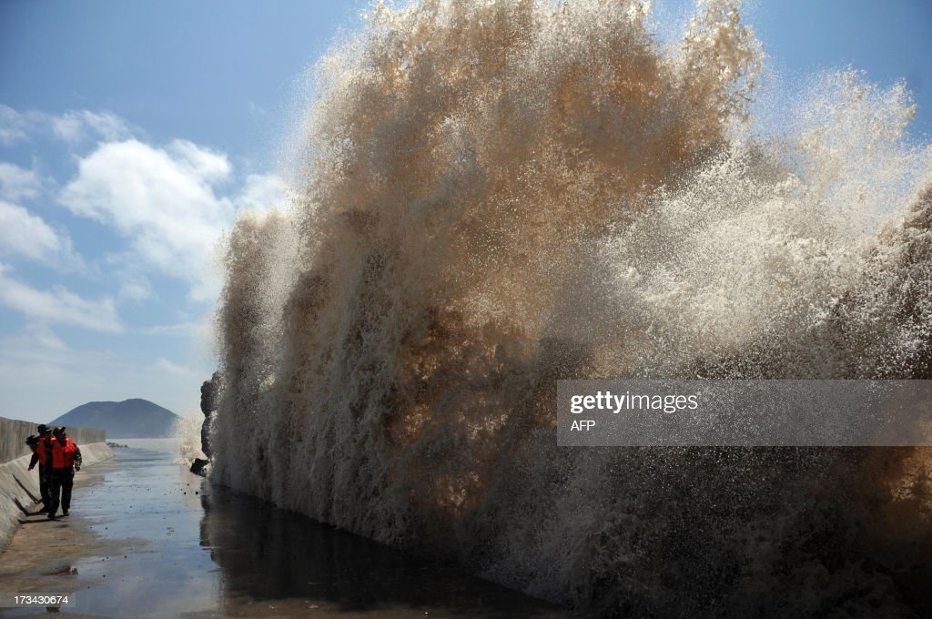 This picture taken on July 12, 2013 shows huge waves surging up against the shoreline of Diaobin fishing port in Wenling city, east China's Zhejiang province. Eastern China was on July 14 bracing for torrential downpours from Typhoon Soulik which forced the evacuation of half a million people after killing two in Taiwan. CHINA