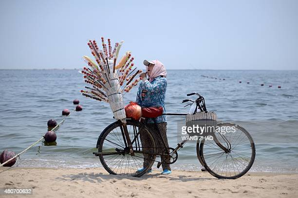 This picture taken on July 14 shows a candied haws vendor standing by her bicycle as she waits for customers on the beach in Qinghuangdao north...