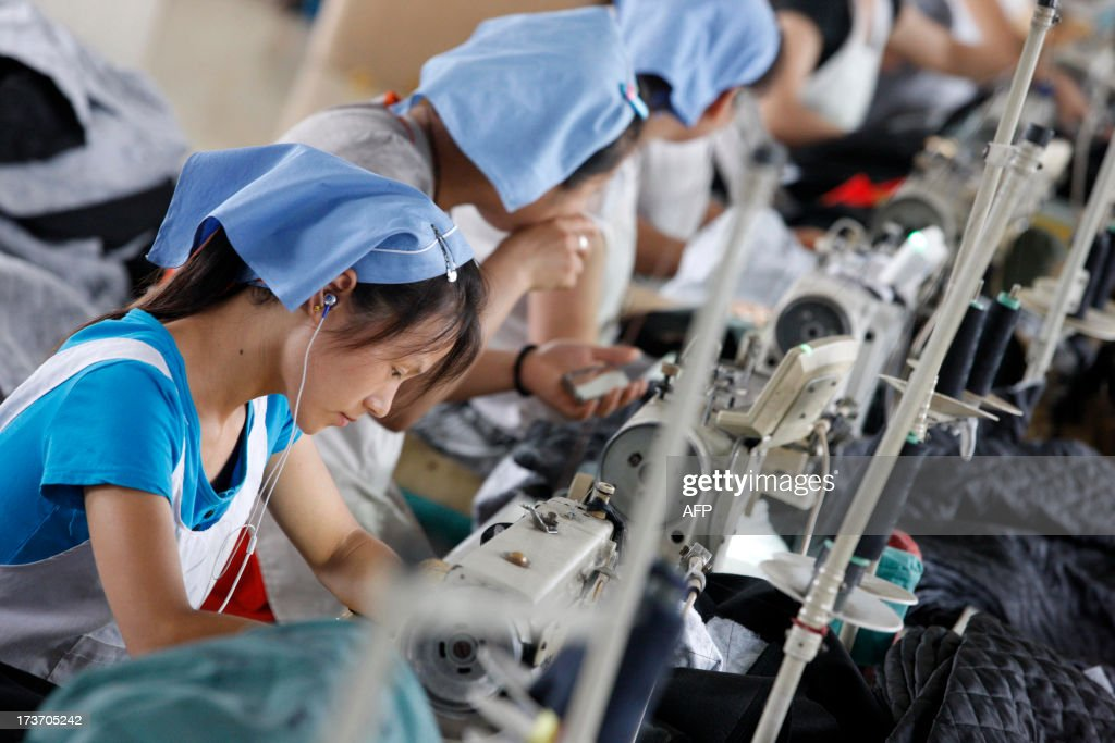 This picture taken on July 15, 2013 shows laborers producing clothes waiting to be exported to EU in a factory in Huaibei, north China's Anhui province. Foreign direct investment (FDI) into China rose 4.9 percent year-on-year during the first half of 2013, official data showed Wednesday, despite slowing growth in the world's second-largest economy. CHINA OUT AFP PHOTO