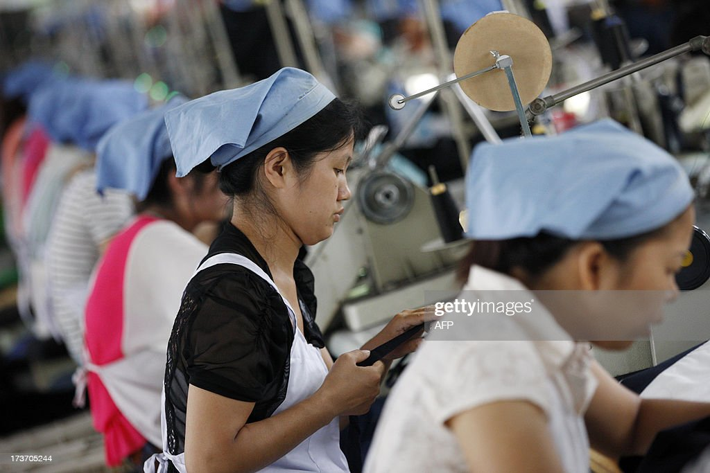 This picture taken on July 15, 2013 shows laborers producing clothes waiting to be exported to EU in a factory in Huaibei, north China's Anhui province. Foreign direct investment (FDI) into China rose 4.9 percent year-on-year during the first half of 2013, official data showed Wednesday, despite slowing growth in the world's second-largest economy. CHINA