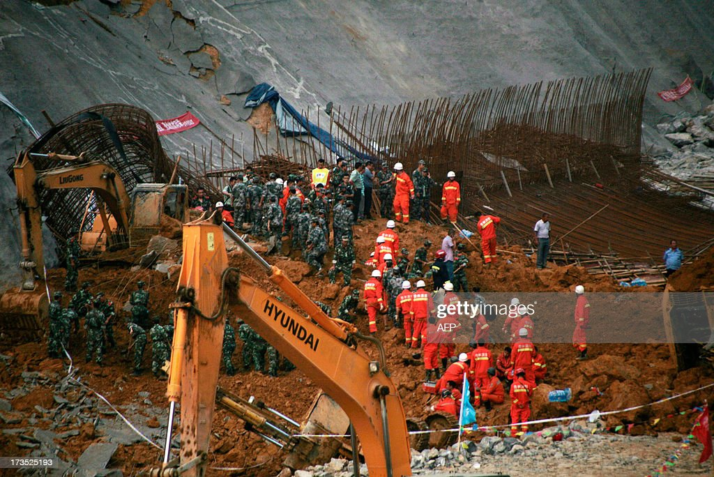 This picture taken on July 15, 2013 shows rescuers looking for victims after a landslide in Bijie, southwest China's Guizhou province. The landslide which happened in the afternoon of July 15 left 5 dead and 8 injuried. At least 295 people have been confirmed dead or missing after rainstorms and Typhoon Soulik hit China, causing floods, landslides and buildings to collapse, the government said July 15. CHINA OUT AFP PHOTO