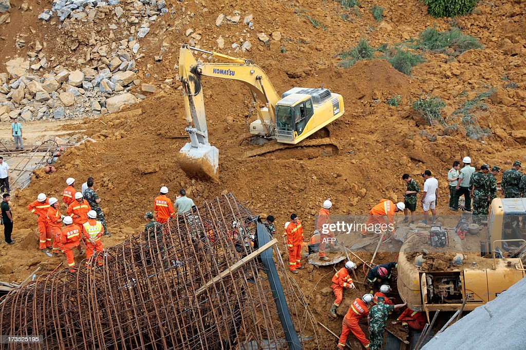 This picture taken on July 15, 2013 shows rescuers looking for victims after a landslide in Bijie, southwest China's Guizhou province. The landslide which happened in the afternoon of July 15 left 5 dead and 8 injuried. At least 295 people have been confirmed dead or missing after rainstorms and Typhoon Soulik hit China, causing floods, landslides and buildings to collapse, the government said July 15. CHINA