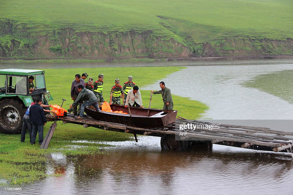 This picture taken on July 15, 2013 shows rescuers relocating victims after they were trapped by floodwaters in Hulunbuir, north China's Inner Mongolia region. At least 295 people have been confirmed dead or missing after rainstorms and Typhoon Soulik hit China, causing floods, landslides and buildings to collapse, the government said on July 15. CHINA