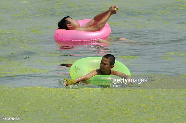 This picture taken on July 15 2015 shows people floating in the waters filled with algae at a beach in Qingdao in eastern China's Shandong province...