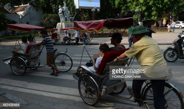 This picture taken on July 16 014 shows foreign tourists enjoying a city tour by cyclos in Hanoi downtown Relations between the communist neighbours...