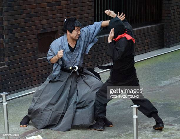 This picture taken on July 16 2014 shows members of pantomime group Gabez clad in a samurai and ninja costums performing at Asakusa shrine in Tokyo...