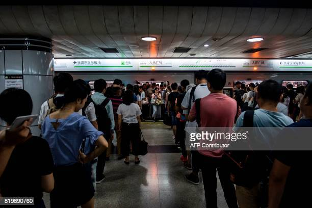 This picture taken on July 19 2017 shows commuters during the morning rush hour at a station of the Shanghai Metro in Shanghai Deep underneath...