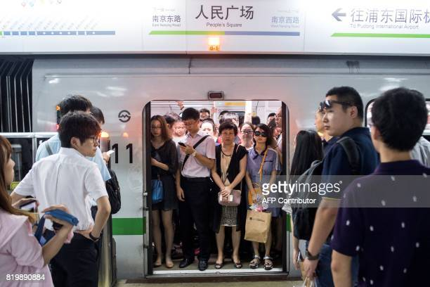 This picture taken on July 19 2017 shows commuters in the morning rush hour on line 2 of the Shanghai Metro in Shanghai Deep underneath Shanghai...