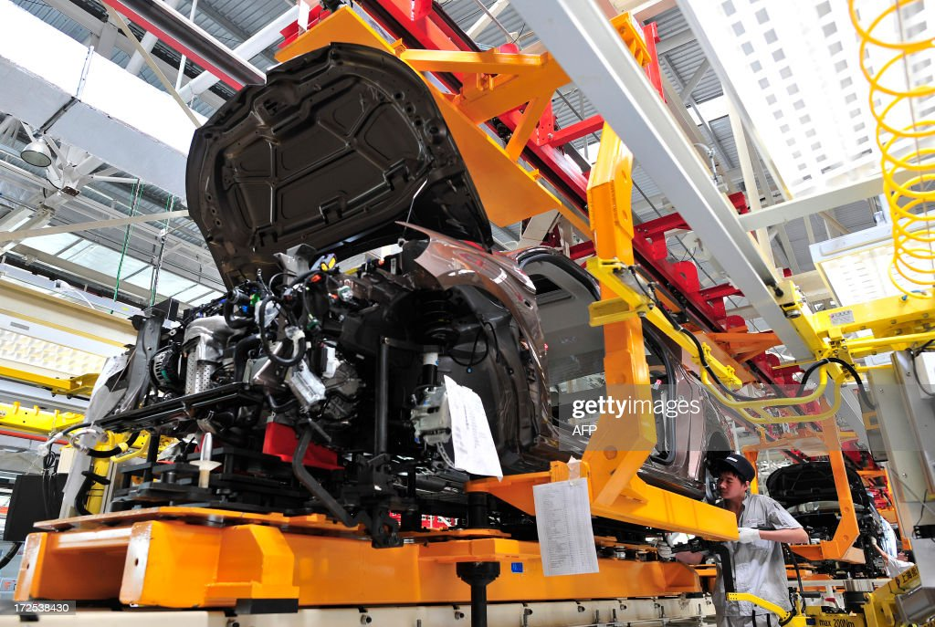 This picture taken on July 2, 2013 shows an employee working on the production line in a new plant of Dongfeng Peugeot-Citroën Automobile Limited (DPCA) in Wuhan, central China's Hubei province. China's second biggest automaker, Dongfeng, has held talks about buying a stake in troubled French car firm PSA Peugeot Citroen, a state-backed newspaper said on July 3. CHINA OUT AFP PHOTO