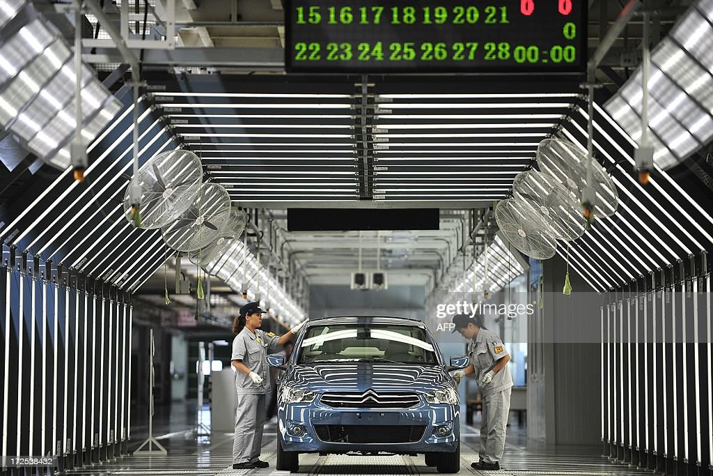 This picture taken on July 2, 2013 shows employees working on the production line in a new plant of Dongfeng Peugeot-Citroën Automobile Limited (DPCA) in Wuhan, central China's Hubei province
