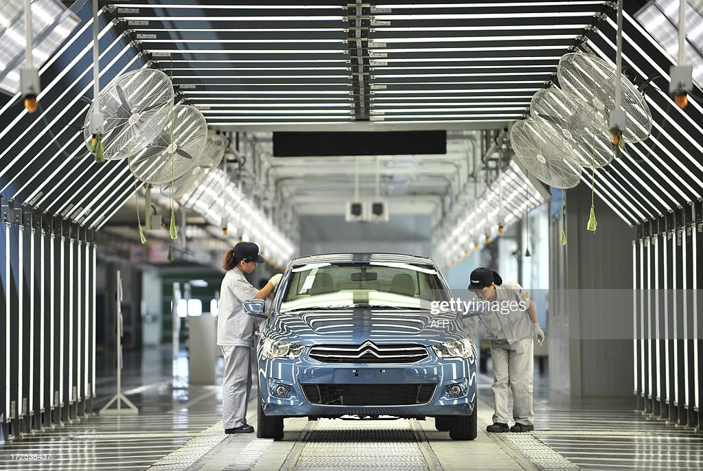 This picture taken on July 2, 2013 shows employees working on the production line in a new plant of Dongfeng Peugeot-Citroën Automobile Limited (DPCA) in Wuhan, central China's Hubei province. China's second biggest automaker, Dongfeng, has held talks about buying a stake in troubled French car firm PSA Peugeot Citroen, a state-backed newspaper said on July 3. CHINA