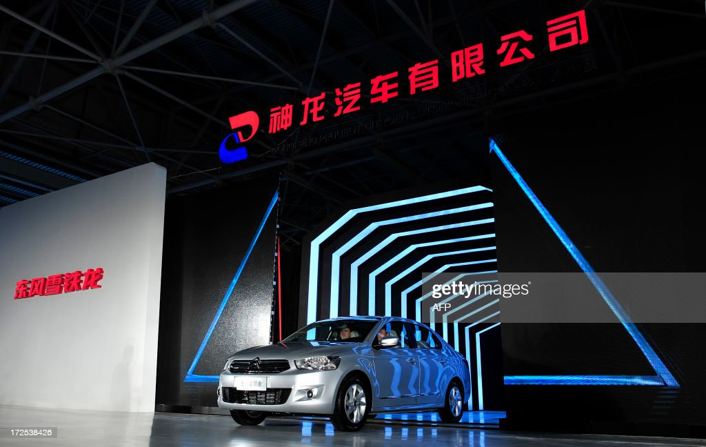 This picture taken on July 2, 2013 shows the first Elysee produced at the new plant of Dongfeng Peugeot-Citroën Automobile Limited (DPCA) in Wuhan, central China's Hubei province. China's second biggest automaker, Dongfeng, has held talks about buying a stake in troubled French car firm PSA Peugeot Citroen, a state-backed newspaper said on July 3. CHINA