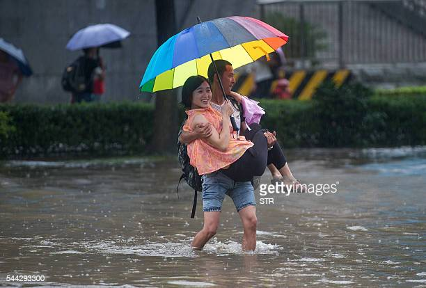 TOPSHOT This picture taken on July 2 2016 shows people crossing a flooded street in Wuhan in China's central Hubei province Authorities on July 2...
